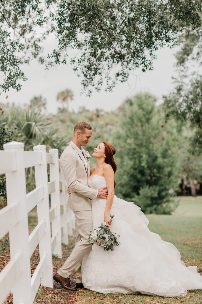 bride and groom posing near classic white farm fence