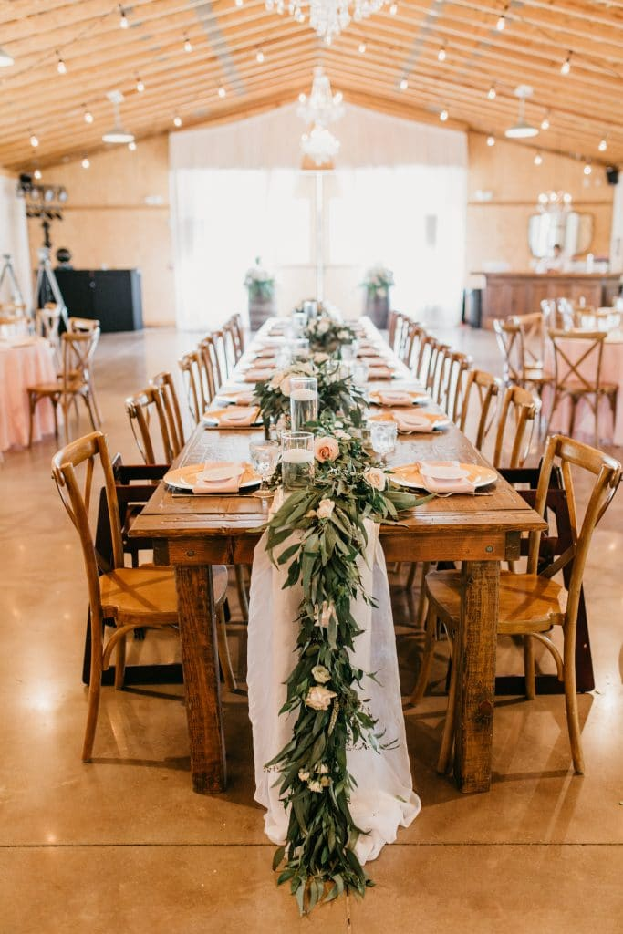 long rustic reception table decorated with runner of green leaves
