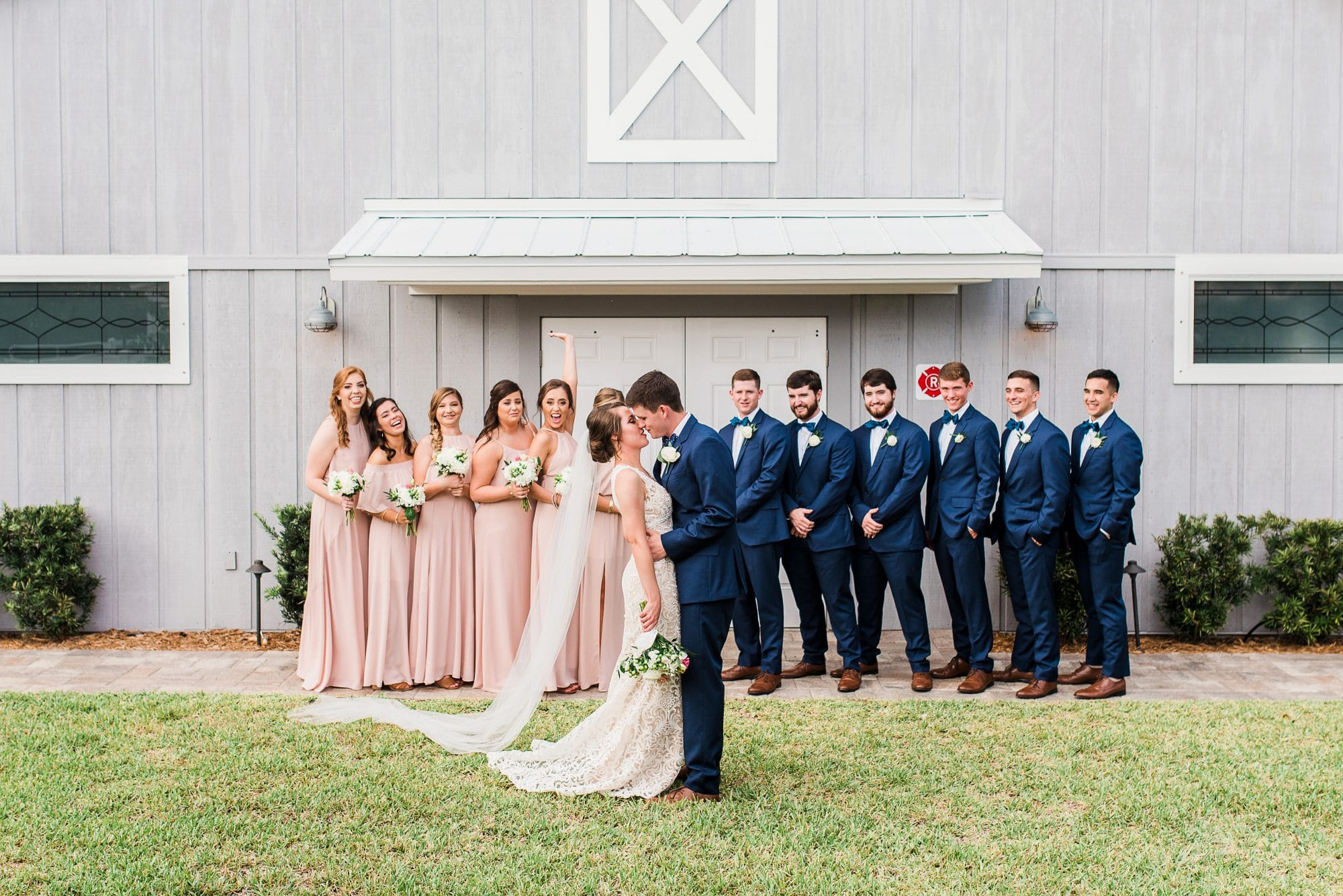 wedding party in front of barn while bride and groom kiss