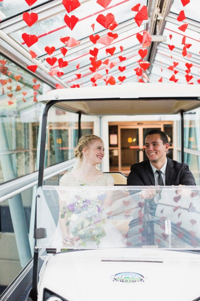 bride smiling at groom as he drives golf cart