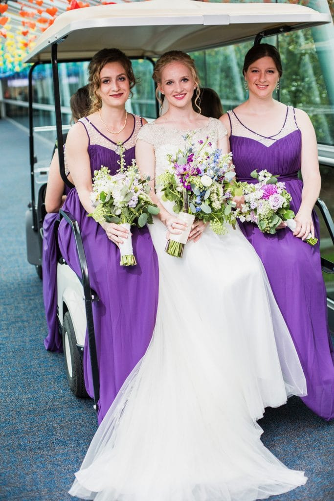 Bride and bridesmaids sitting on back of golf cart