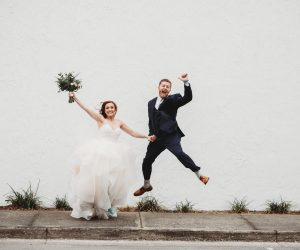 bride and groom jumping in air celebrating