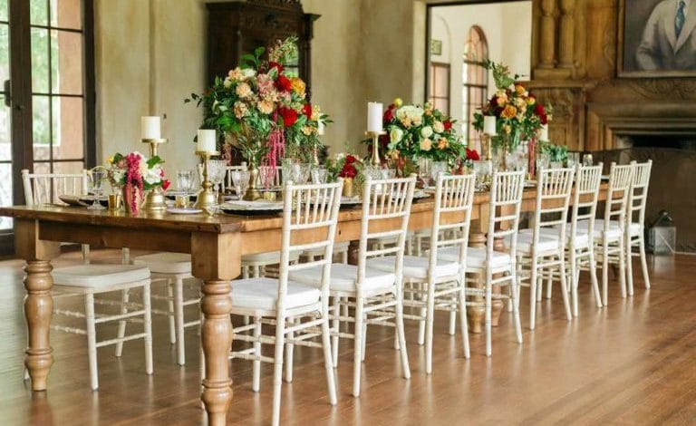 A Chair Affair - white chiavari chairs at long rustic table