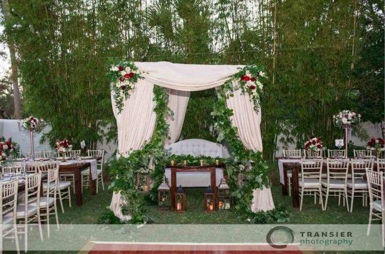 Sweetheart table under canopy in the middle of outdoor reception space