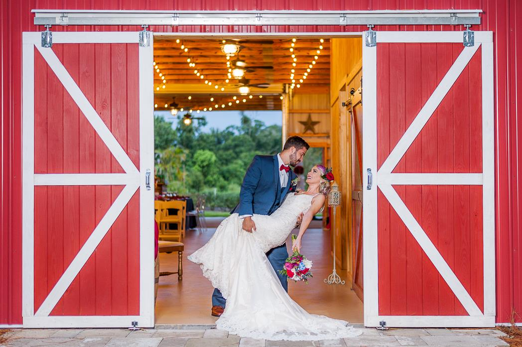 Groom dipping bride in the barn doorway at Blue View Event Barn