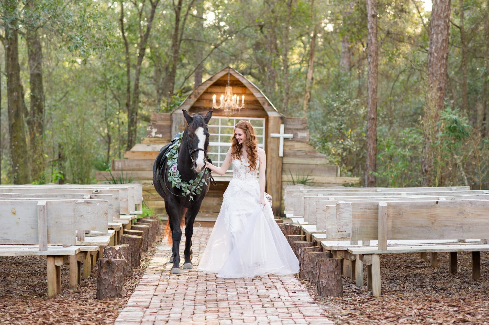 Bride and horse in the ceremony aisle at Bridle Oaks Barn