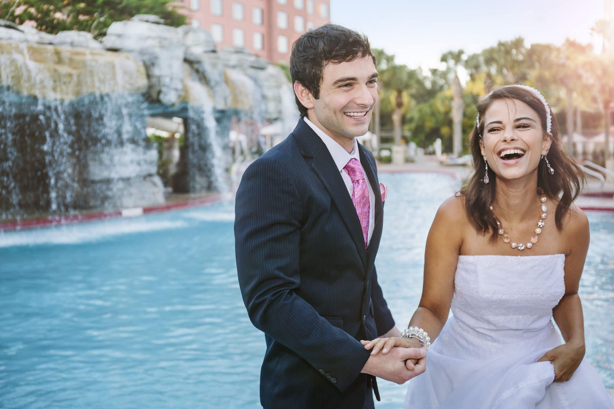 Laughing bride and groom next to the waterfall pool at Caribe Royale