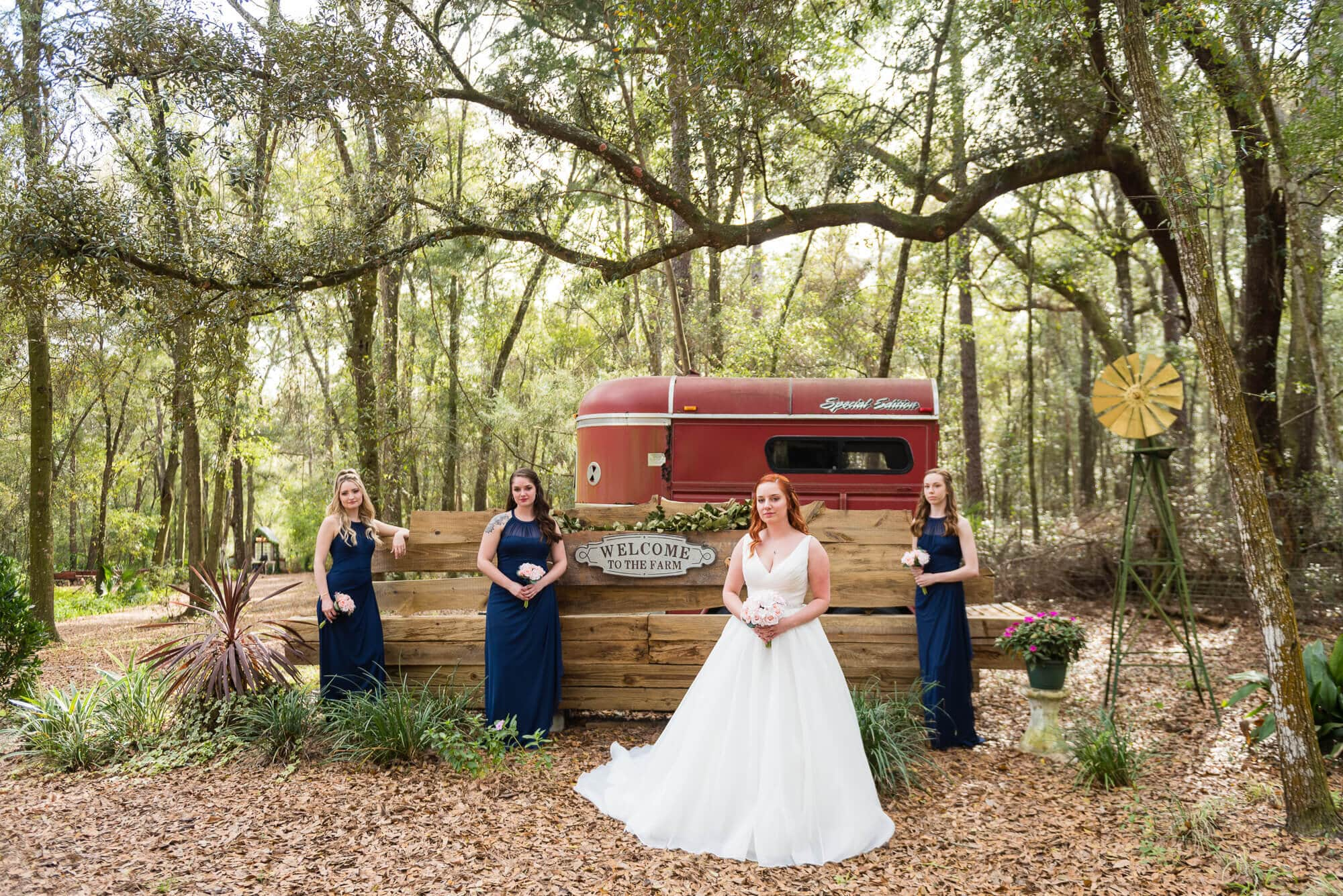 Lori Barbely Photography, bride with bridesmaids in the woods with a horse trailer behind them