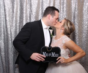 Photo and Video Booths - newlyweds kissing with Mr. and Mrs. sign