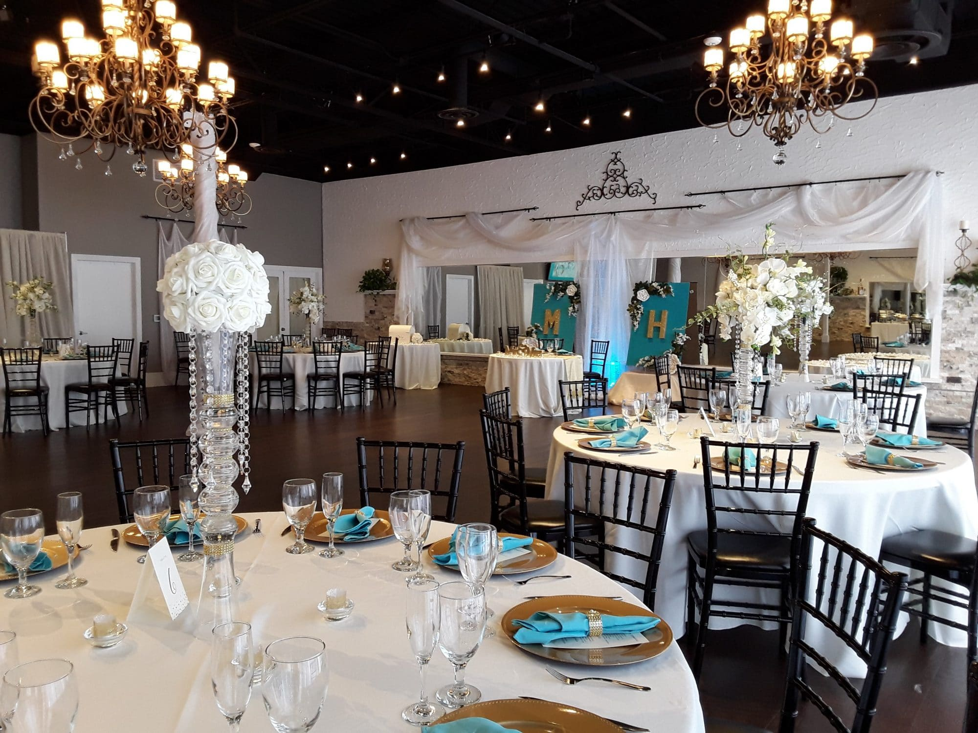 White and gold reception room with touches of turquoise at Rhythm & Smooth.