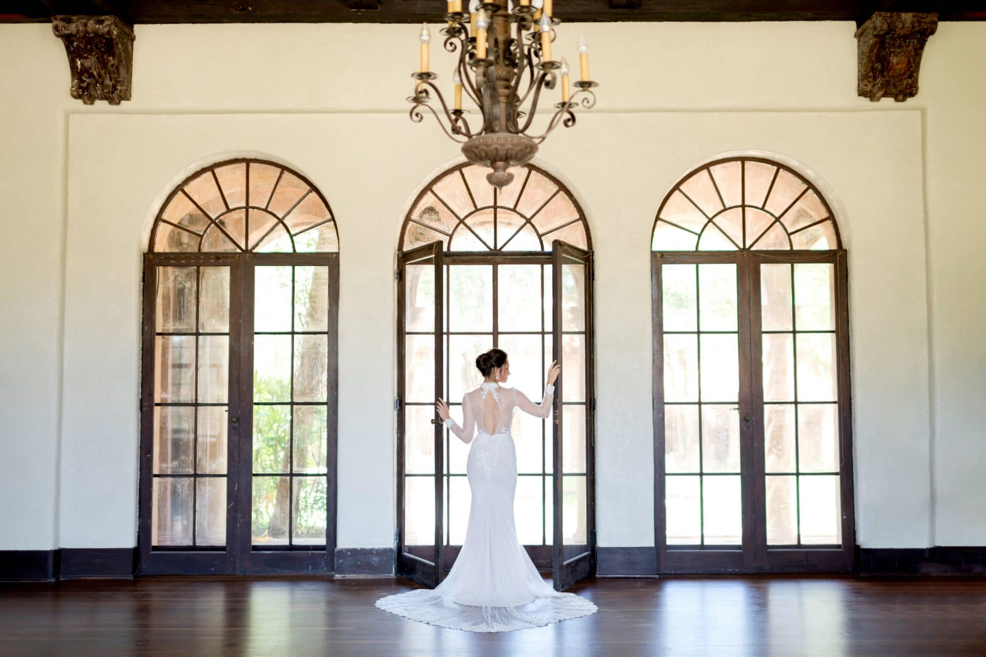 Bride looking out one of the tall french doors at The Howey Mansion