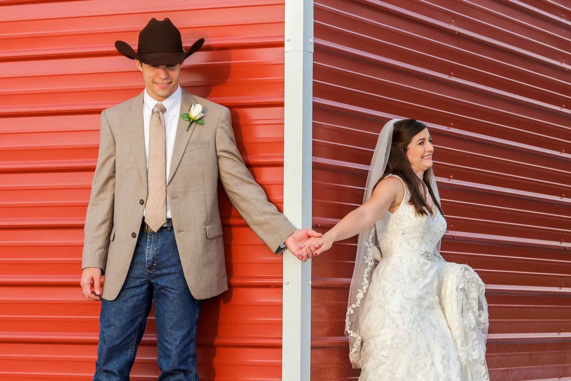 "bride and groom sharing ""first touch"" around corner of barn at Diamond L Venue"