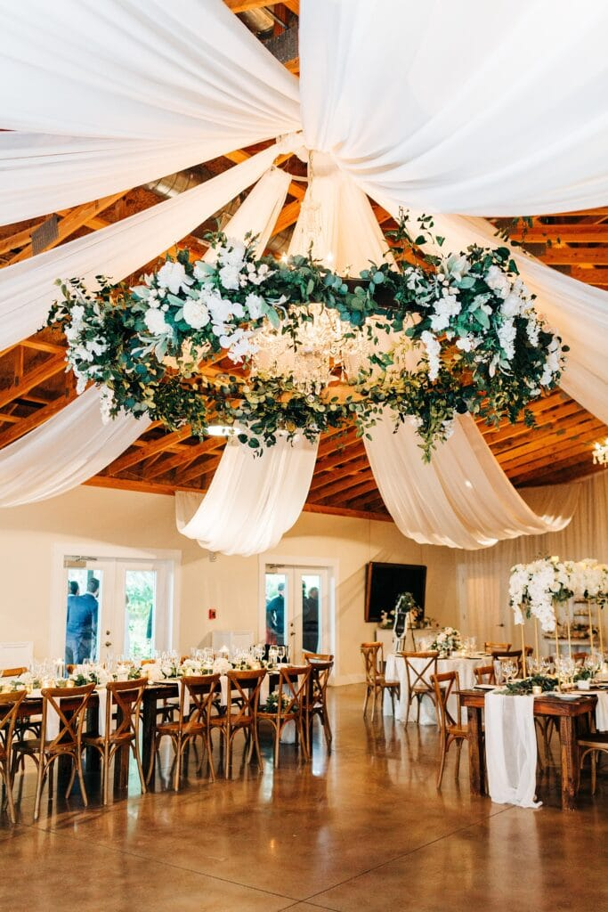 fabric draped on ceiling with greens over tables