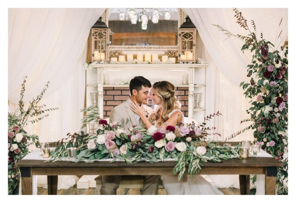 Harmony-Haven-Events-Bride and Groom kissing at main table with rustic chic decorations