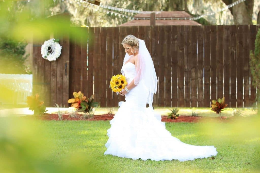 Harmony-Haven-Events-Bride posing looking at sunflower bouquet outdoors