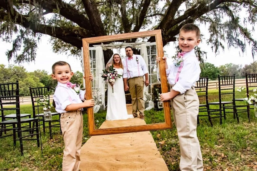 TrueHeart-Ranch-Two little children holding wooden frame in front of bride and groom
