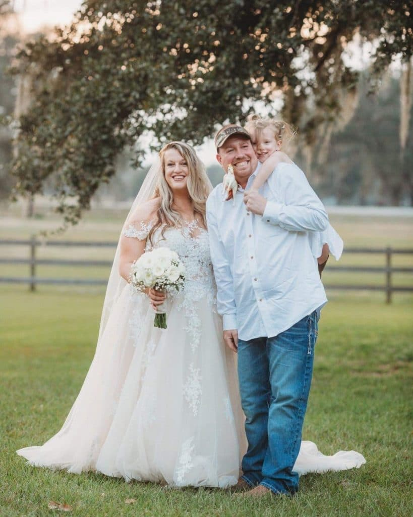 TrueHeart-Ranch-Bride and groom standing by tree with daughter on his back