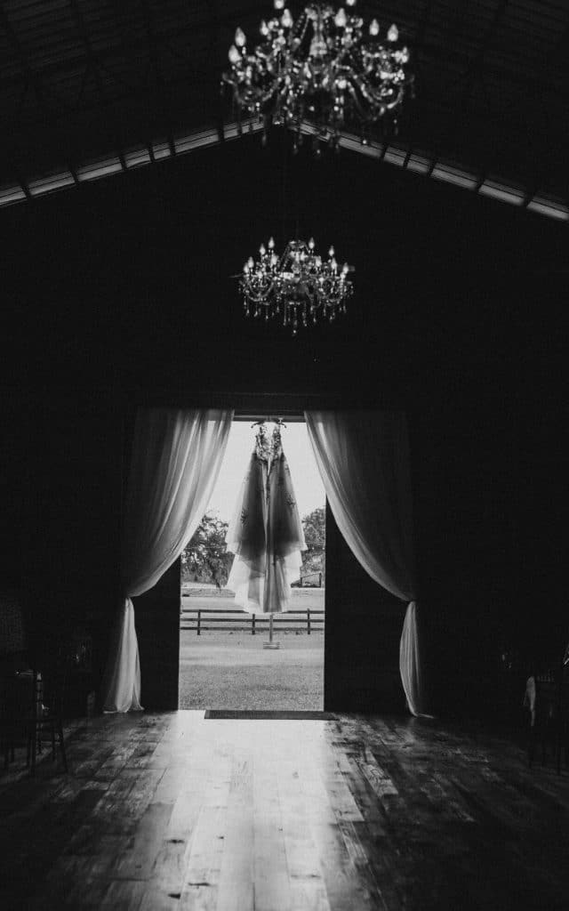 TrueHeart-Ranch- Black and white image of a wedding dress hanging in the doorway of the Barn