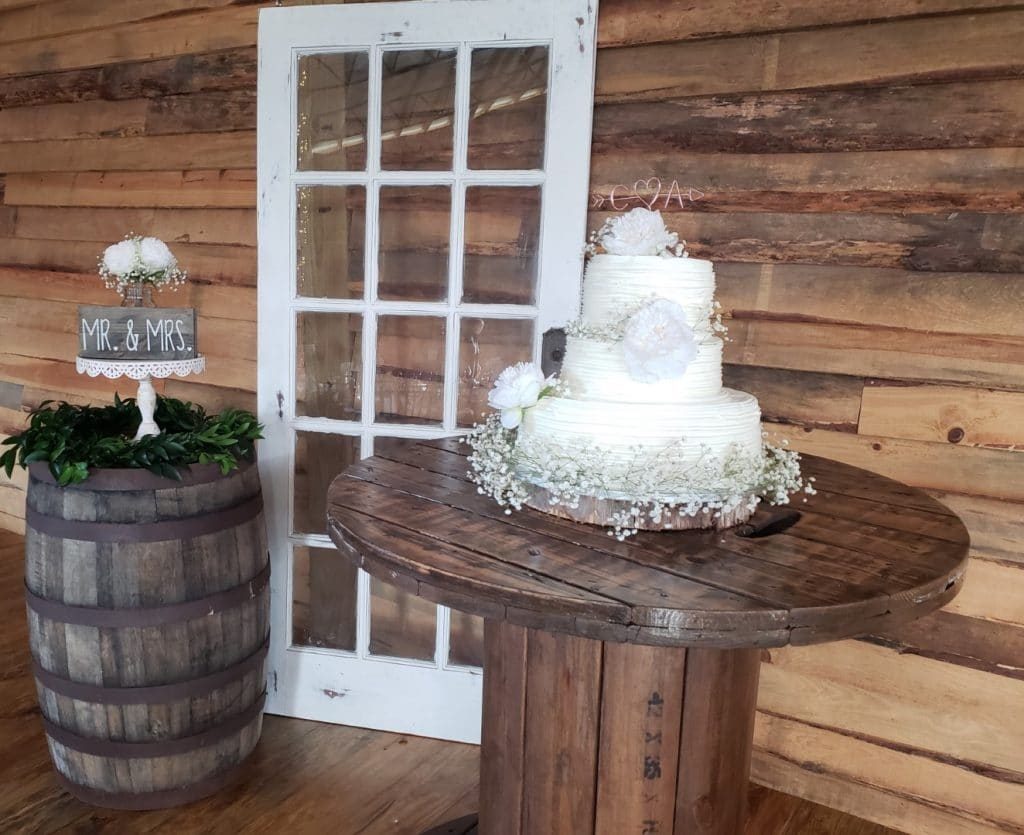 TrueHeart-Ranch- Wedding cake on a large wooden pedestal next to a wooden barrel.