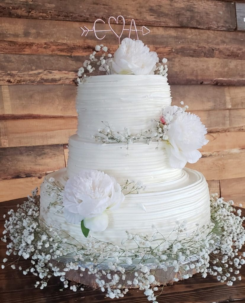 TrueHeart-Ranch-Three tier white wedding cake with babysbreath and white floral decorations