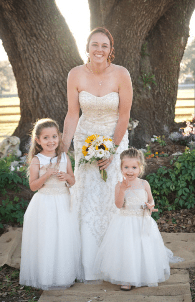 TrueHeart-Ranch- Bride holding bouquet standing with two small children in fancy dresses