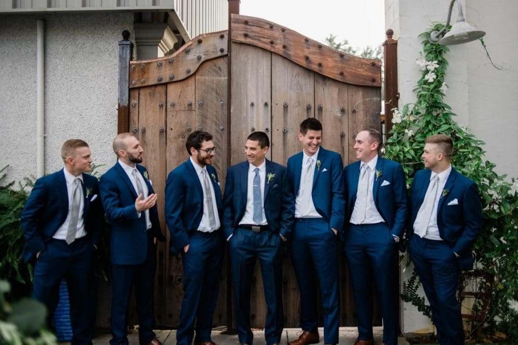 Venue-650-Groomsmen standing in front of large wooden gate