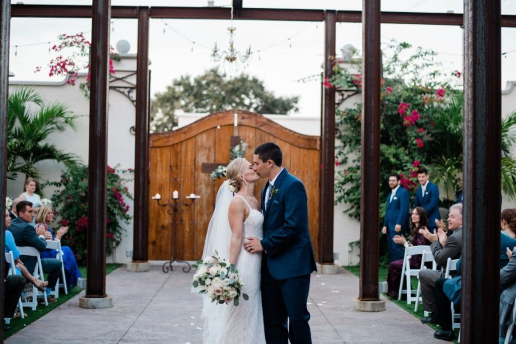 Venue-650-Bride and Groom kissing in courtyard in front of large wooden gate