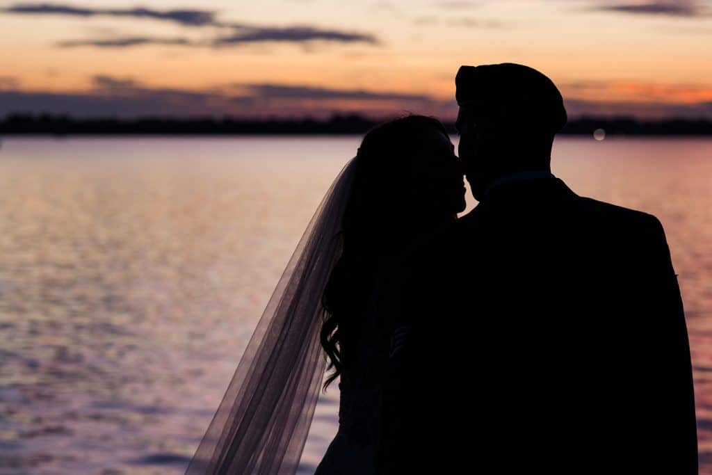 Bride and groom silhouette overlooking ocean