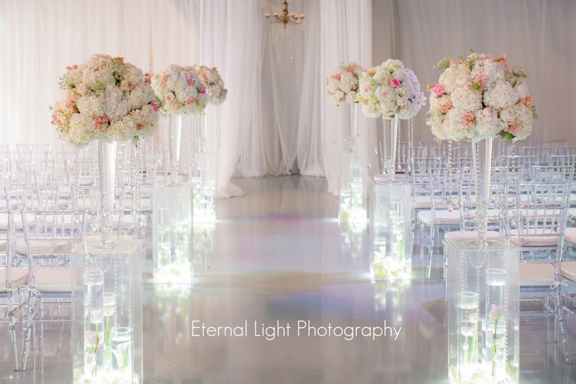 Atmospheres Floral and Decor - transparent ceremony chairs and towering aisle decorations with pink hydrangeas