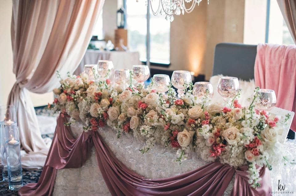 Atmospheres Floral and Decor - sweetheart table with mauve draping, mercury glass goblet votives, and dense floral arrangement