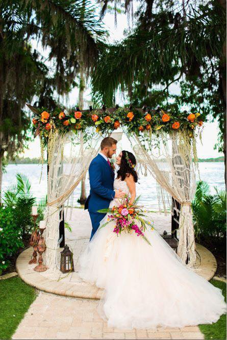 Atmospheres Floral and Decor - bride and groom under pergola decorated with orange blooms and sheer curtains