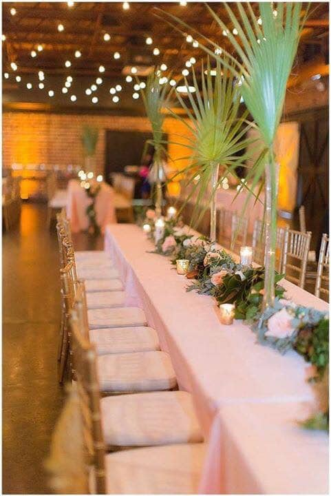 Atmospheres Floral and Decor - long reception table with palm frond centerpieces