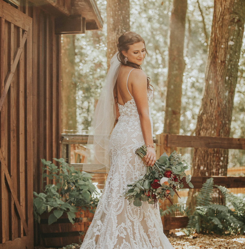 Bridle Oaks Barn - Bride posing outdoors next to small wooden building.