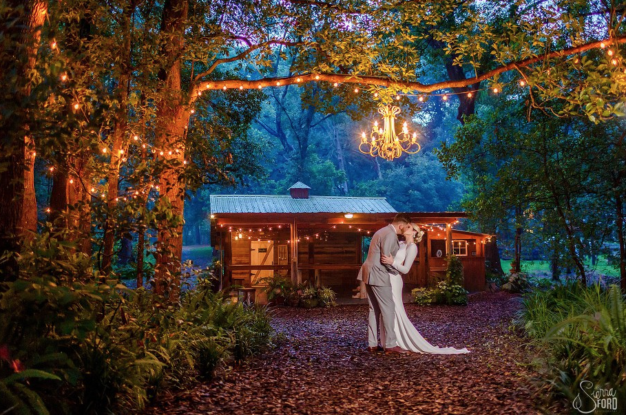 Bridle Oaks Barn - bride and groom outdoors underneath chandelier hanging from tree branch