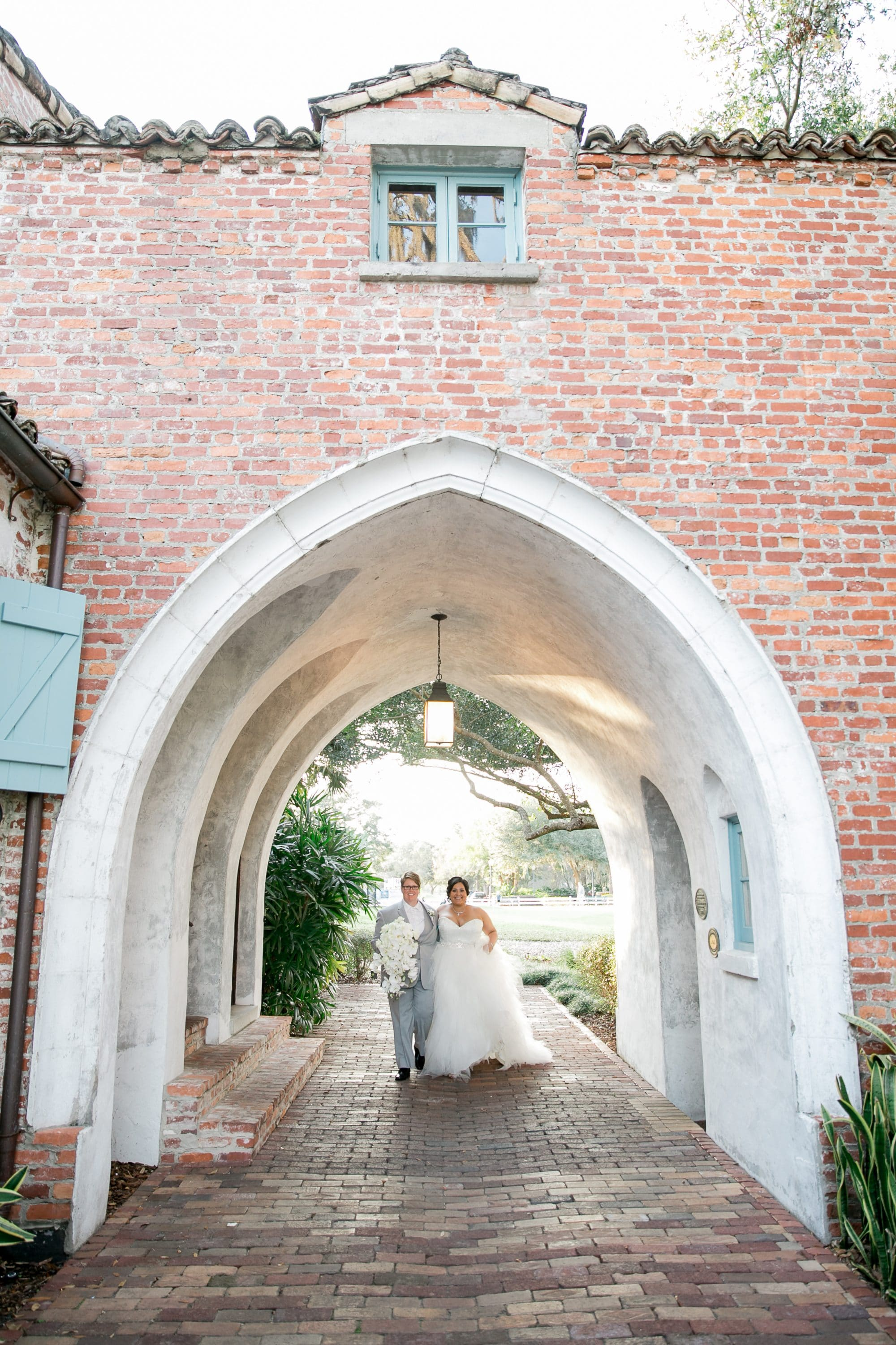 Casa Feliz - brides walking through arched hallway outdoors