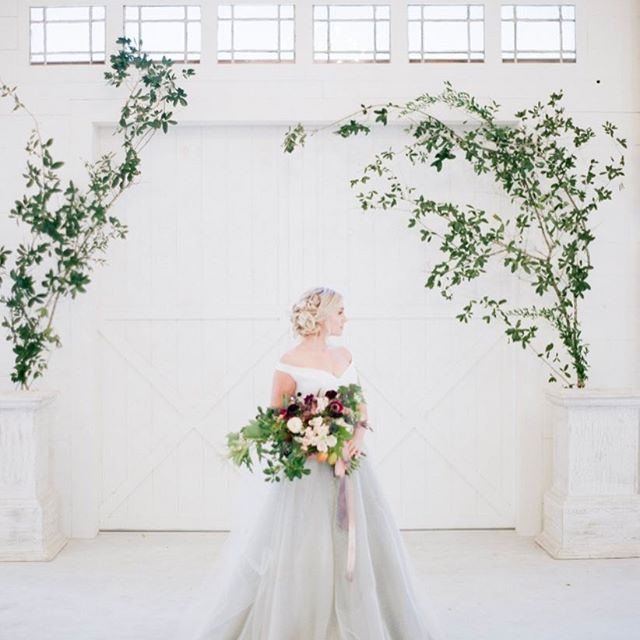 Chandler Oaks Barn - bride with bouquet in all-white room