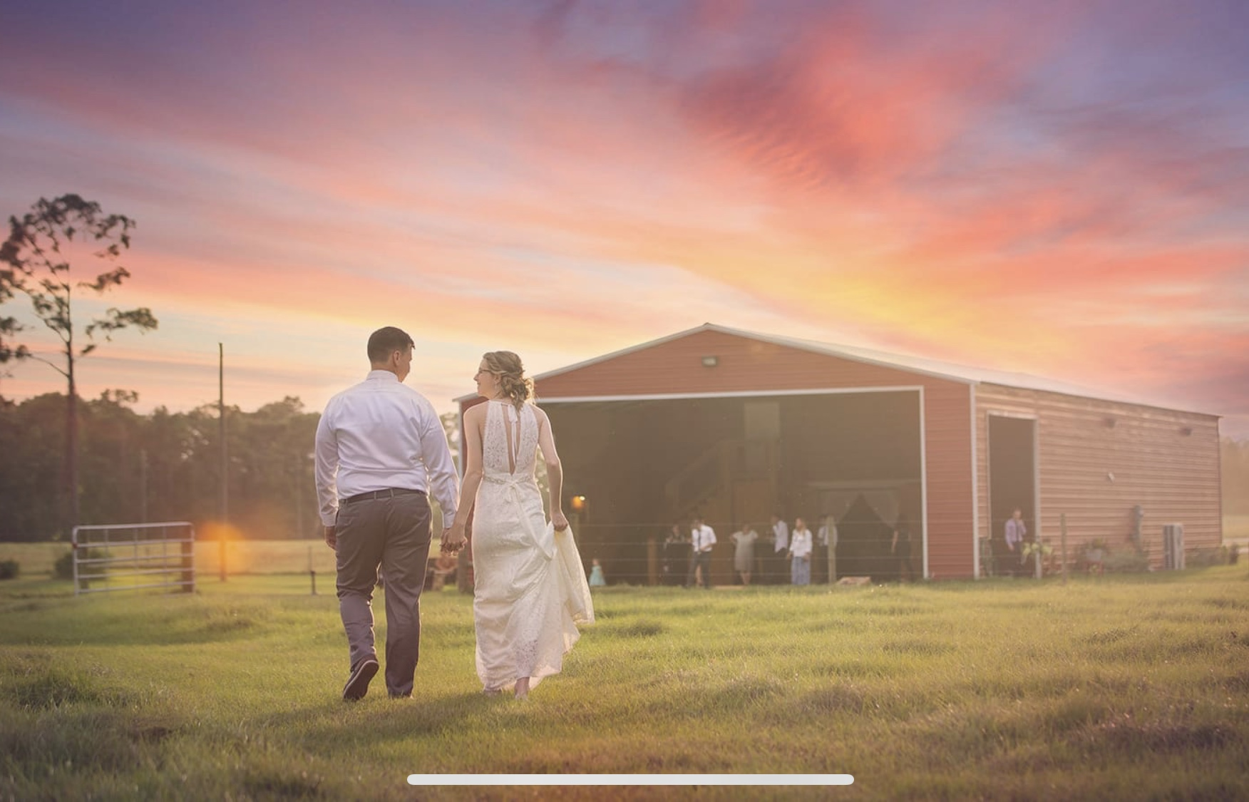 Diamond L Venue - bride and groom walking toward large red barn
