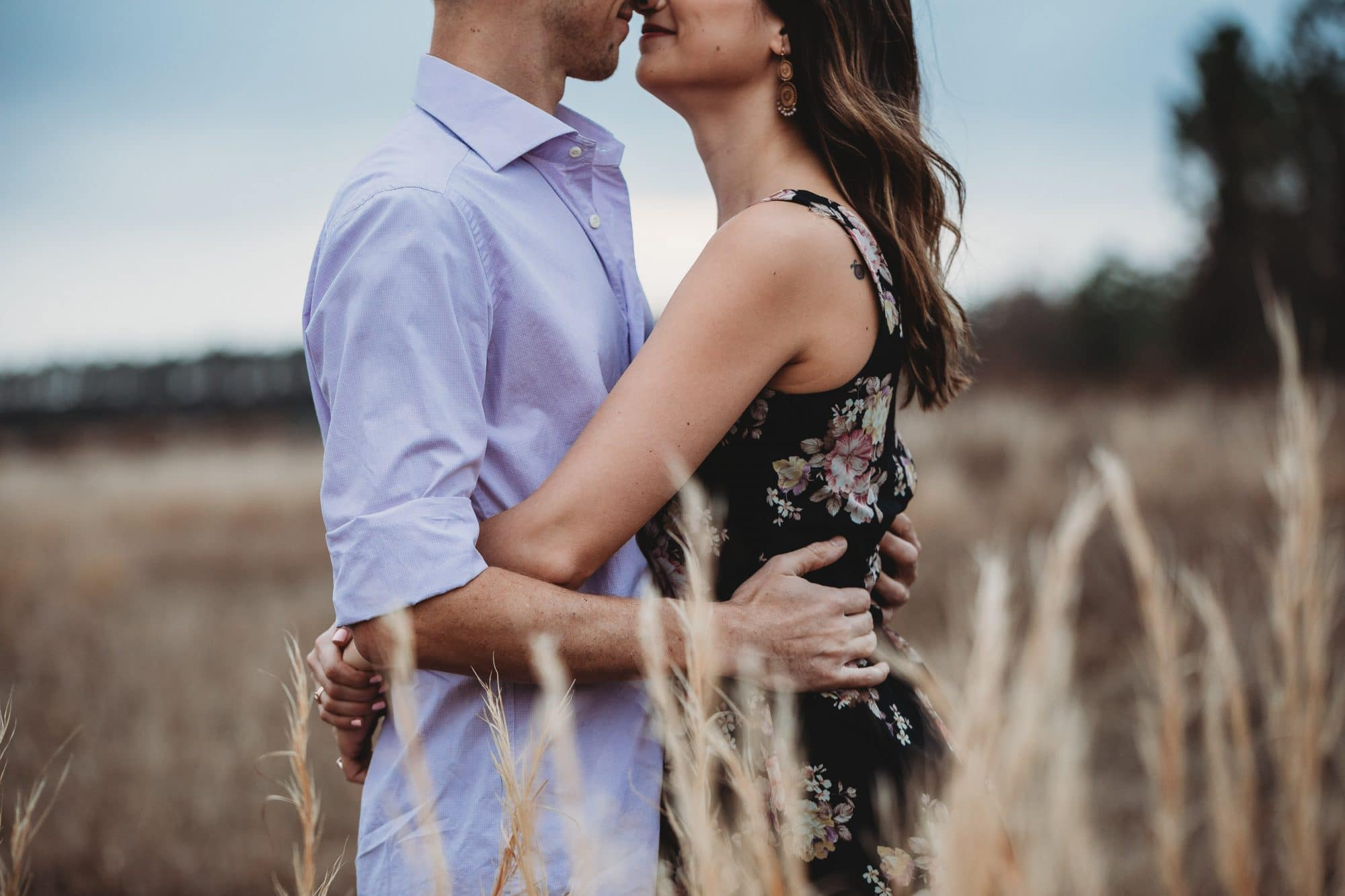 Rachel Doyle Photography - engaged couple holding each other in field