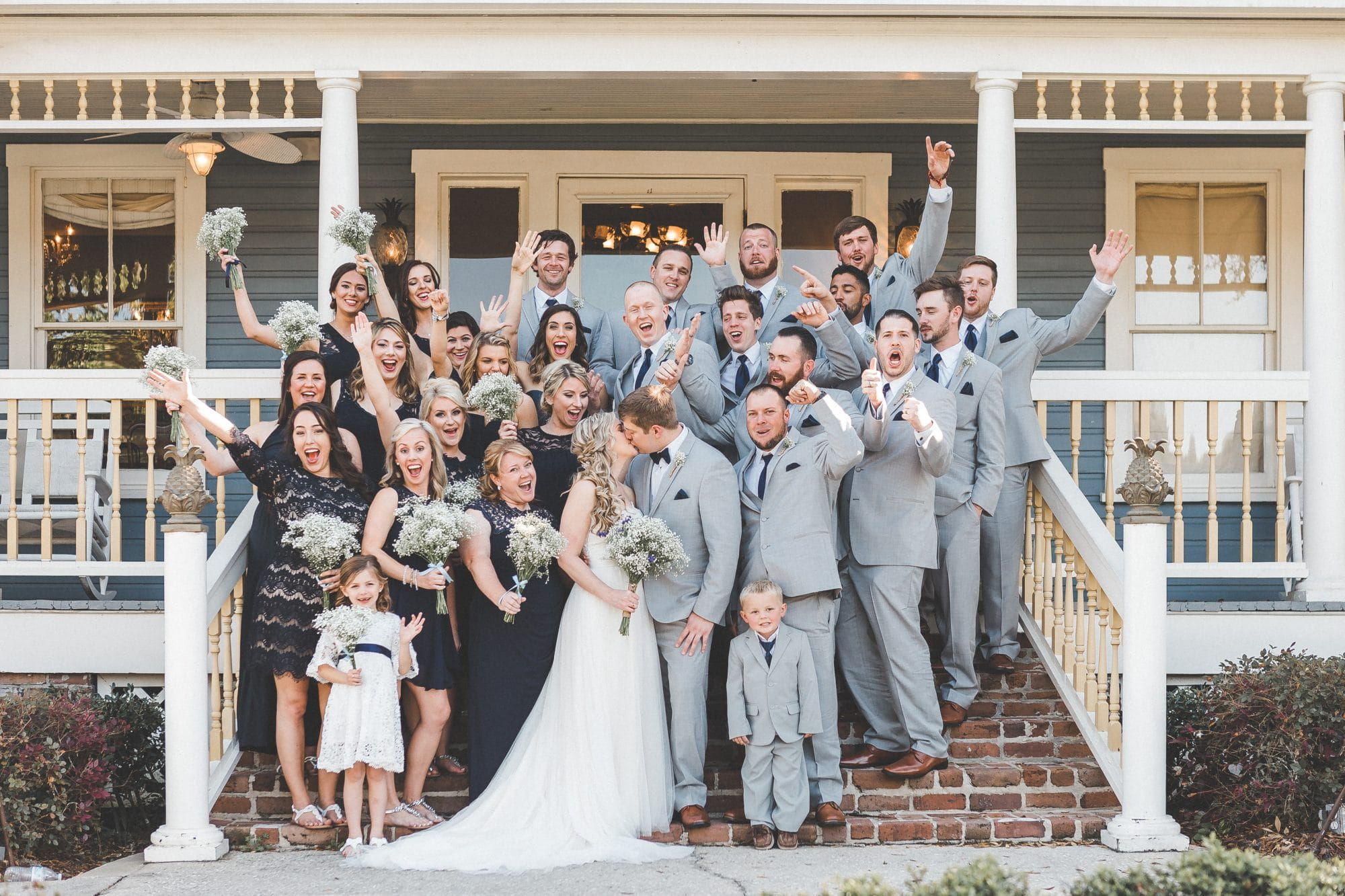Rachel Doyle Photography - bride and groom kiss surrounded by cheering wedding party