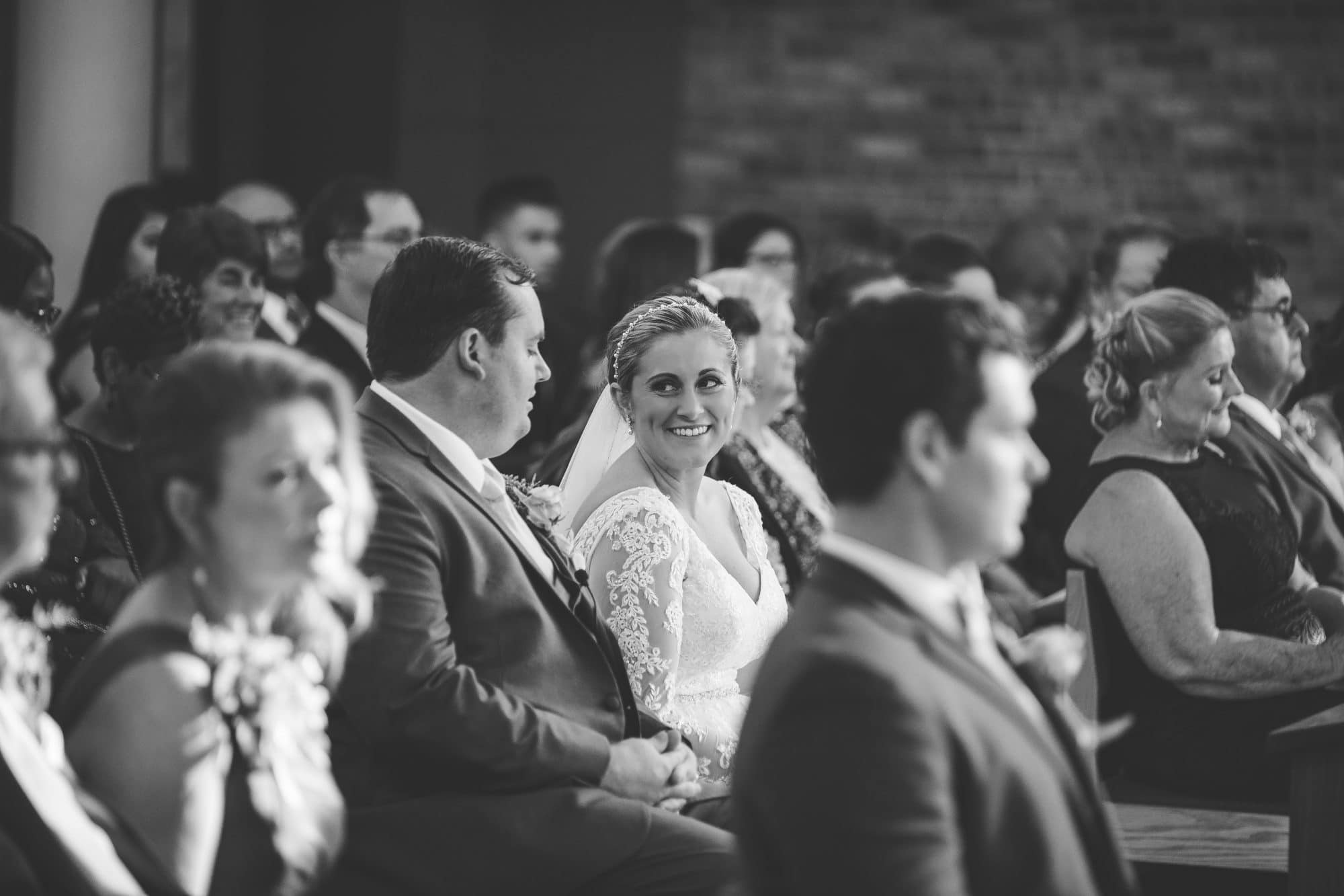 Rachel Doyle Photography - bride and groom smile at each other while seated among guests at ceremony