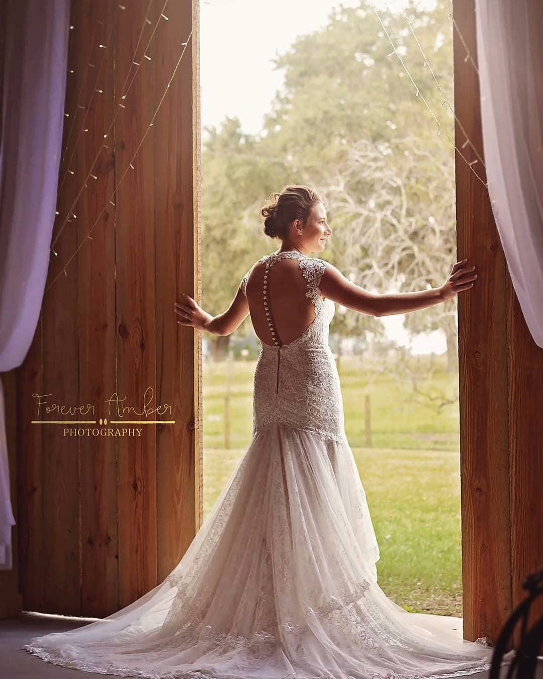 The Barn at Lazy P Ranch - bride looking out of barn doors