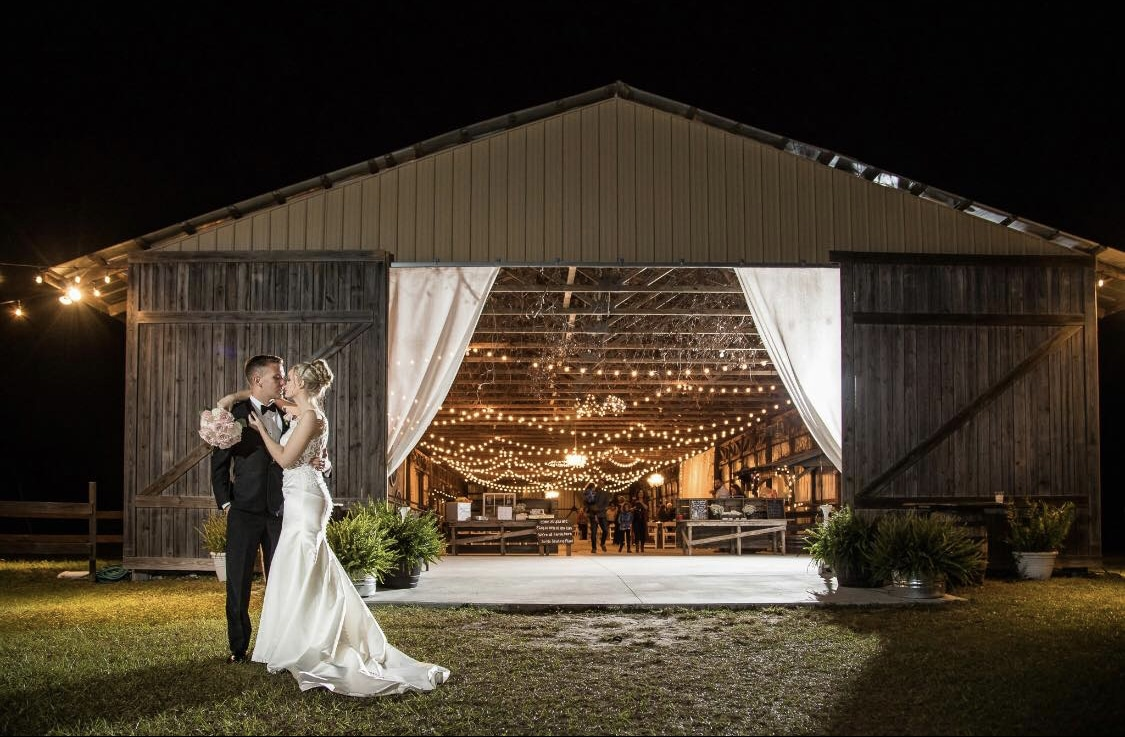 The Barn at Mazak Ranch - bride and groom outside of cute barn strung with market lighting