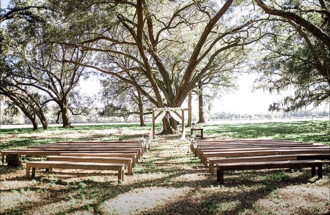 The Barn at Mazak Ranch - ceremony set up with long benches and rustic wooden arch