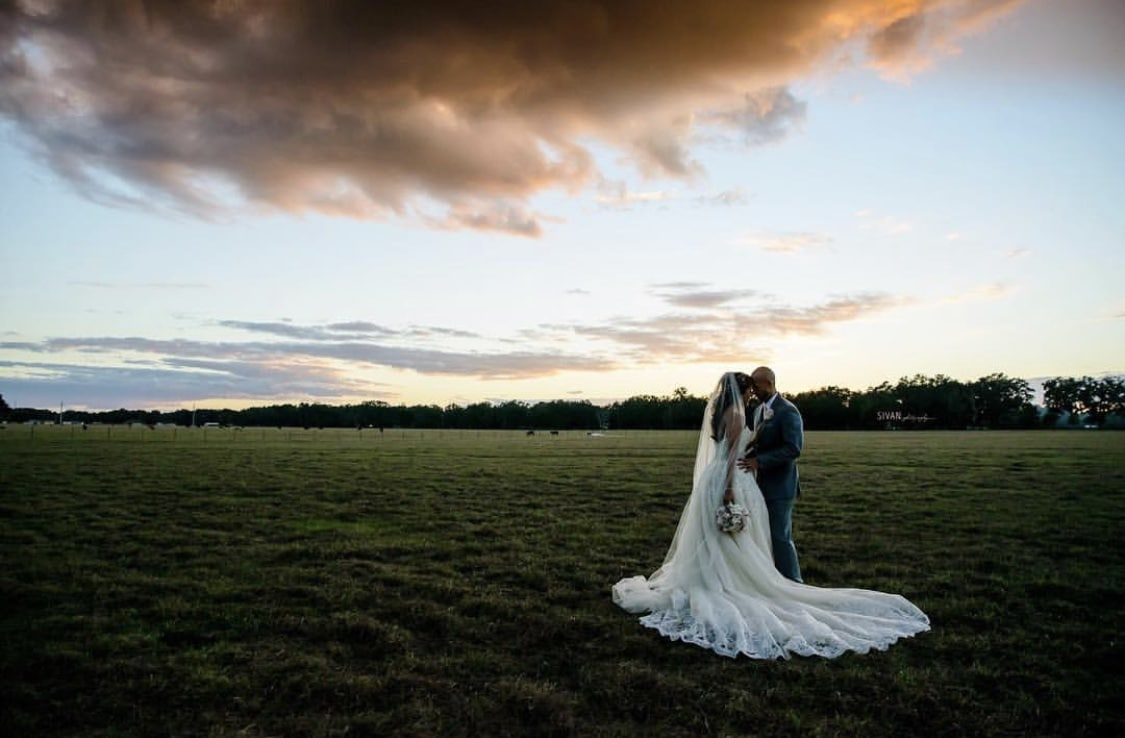 The Barn at Mazak Ranch - bride and groom sharing intimate moment in open field