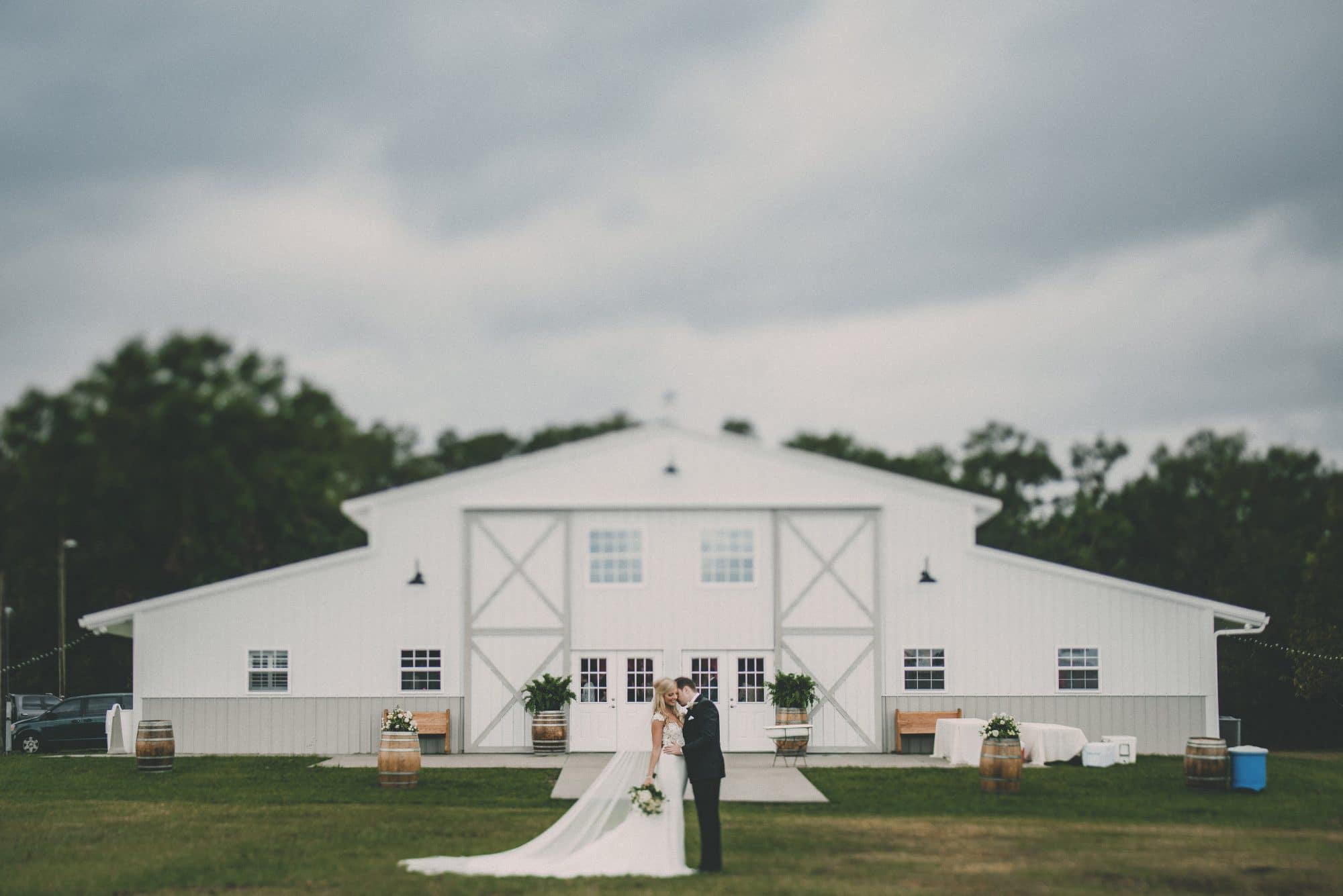 The Barn at Waller Ranch - couple kissing outside of cute white barn