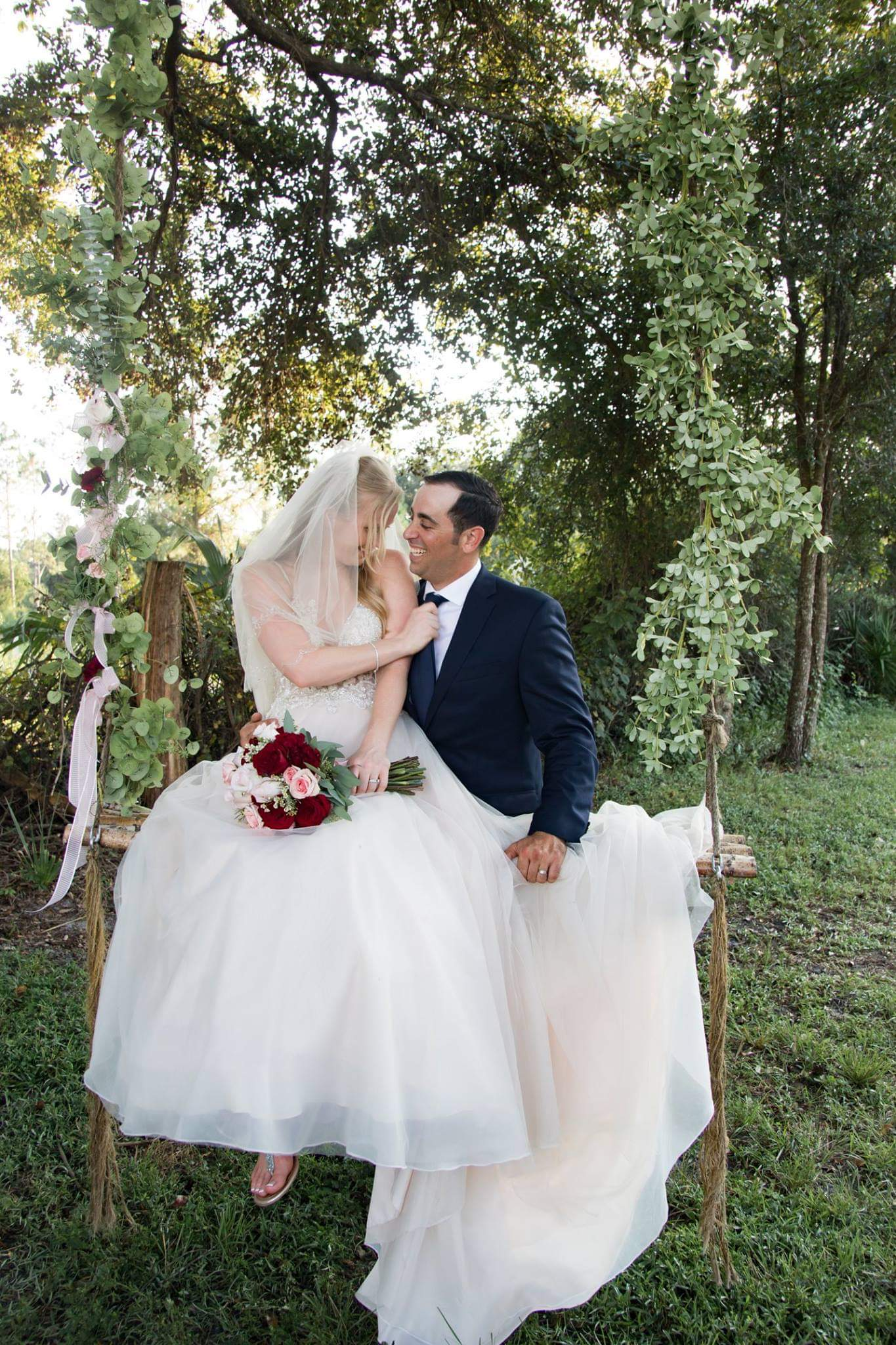The Enchanting Barn - bride and groom on outdoor swing