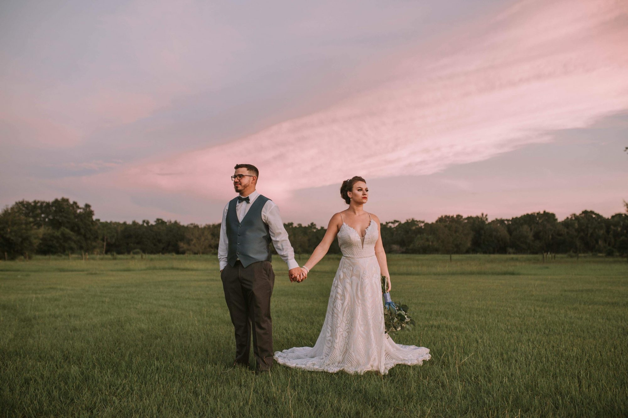 The Orange Blossom Barn - bride and groom holding hands in field
