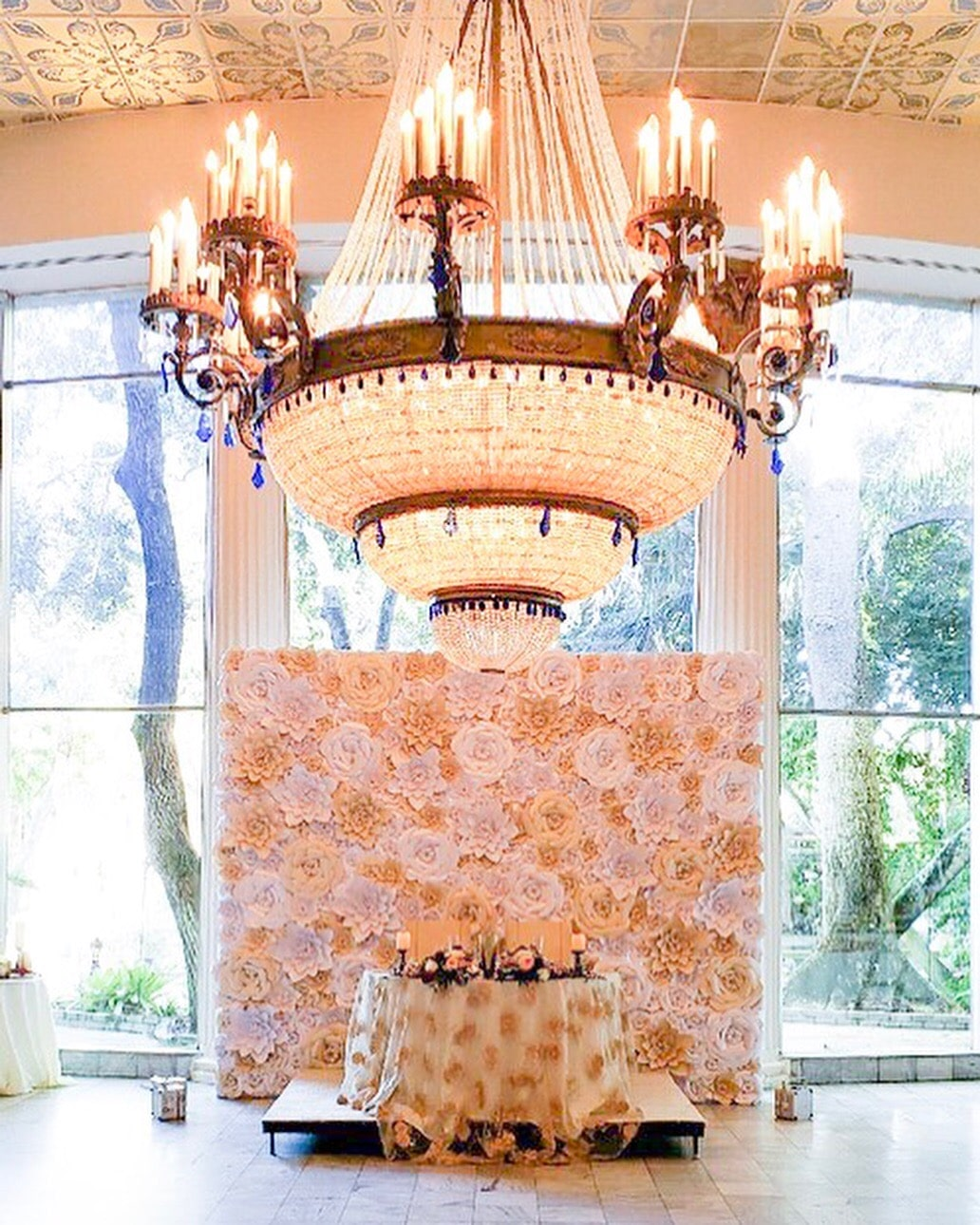 Dazzling Deco - stunning chandelier hanging over sweetheart table that is backed by champagne paper flower backdrop