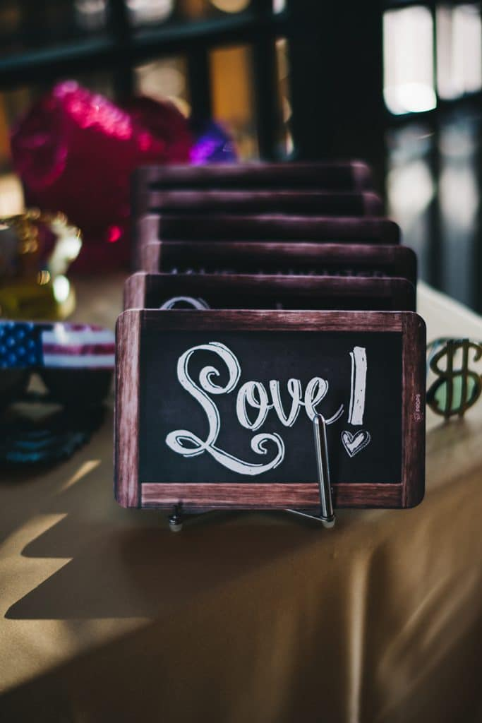 "chalkboard ""love"" sign on photo booth prop table"