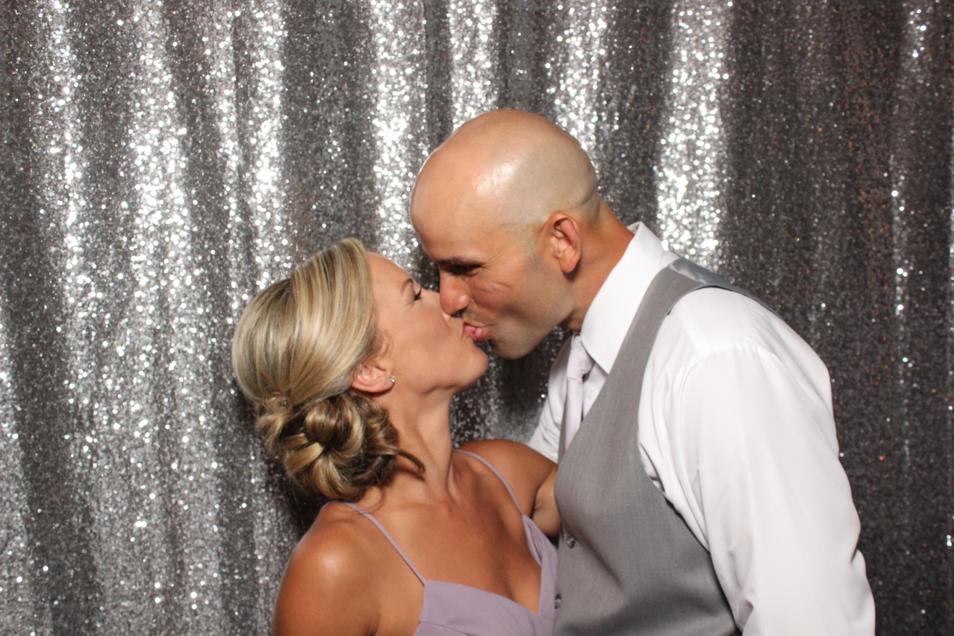 couple kissing in front of silver glitter backdrop